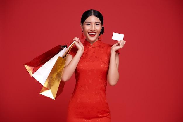 Glückliche asiatische shopaholic frau, die traditionelles cheongsam qipao kleid trägt, das kreditkarte und einkaufstasche auf rot hält. frohes chinesisches neujahr