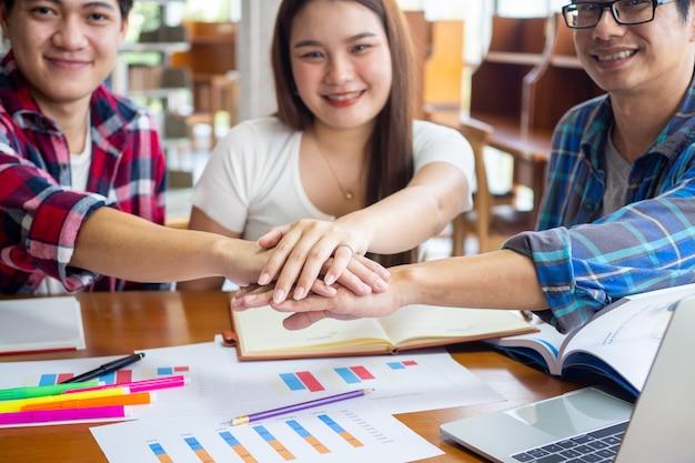 Glückliche asiatische studenten, die gemeinsam ein brainstorming durchführen, um im klassenzimmer der universität mathematische statistiken zu lernen und zu studieren