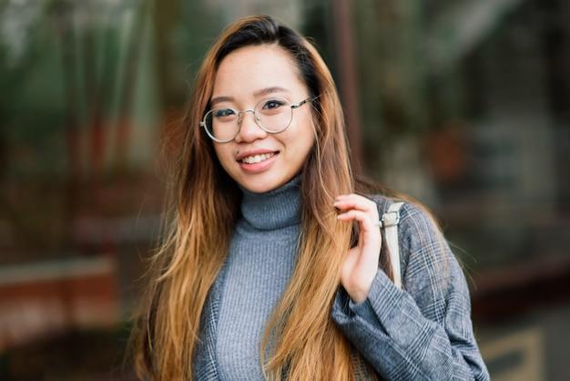 Glückliche asiatische studentin auf der stadtstraße, bildungskonzept
