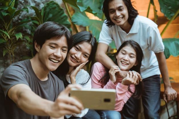 Glückliche asiatische teenager, die selbst fotos machen und spaß haben
