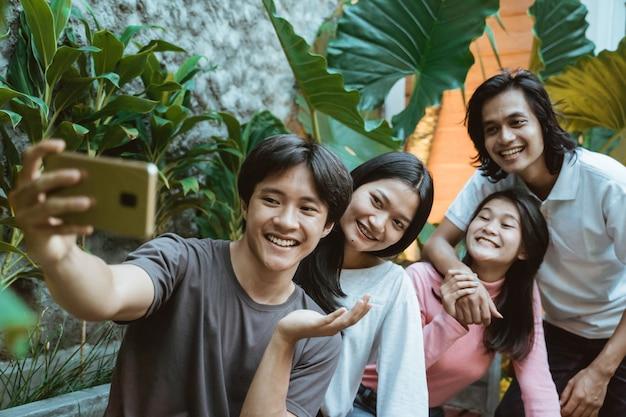 Glückliche asiatische teenager mit smartphone, die im café beim abhängen fotografieren