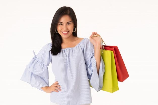 Glückliche asiatische tragende einkaufstaschen der jungen frau lokalisiert