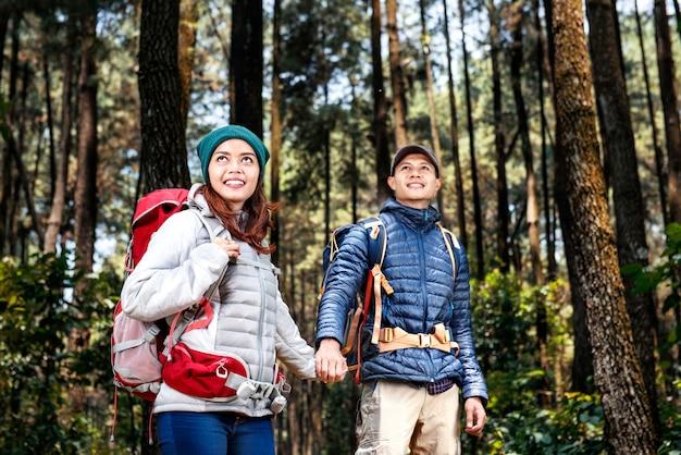 Glückliche asiatische wanderer verbinden mit dem gehenden rucksack beim händchenhalten