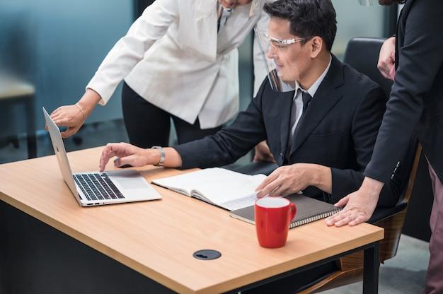 Glückliche asiatische weibliche managerberatung und zusammenarbeit mit kollegen, die mit laptop am schreibtisch im büro arbeiten