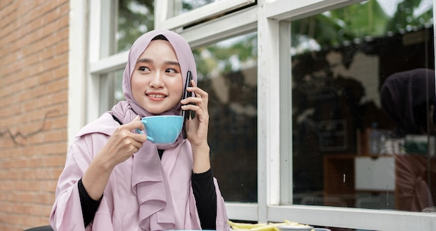 Glückliche asien-hijab-frau, die smartphone benutzt und anruft, kaffee trinken, während im café sitzen