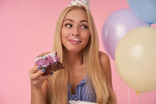 Glückliche attraktive blonde dame, die aufrichtig lächelt und mit feinkostkuchen in ihrer hand beiseite schaut, feiertag feiert, der festliche kleidung trägt und über rosa hintergrund mit sahne auf ihrem mund aufwirft