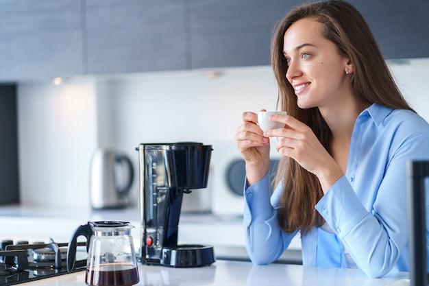 Glückliche attraktive frau, die heißen frischen aromatischen kaffee trinkt, nachdem kaffee mit kaffeemaschine in der küche zu hause gebrüht wird. kaffeemixer und haushaltsküchengeräte für macht heiße getränke
