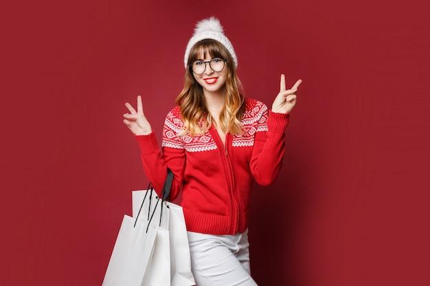 Glückliche attraktive frau im weißen wollhut und im roten winterpullover, der mit einkaufstaschen aufwirft
