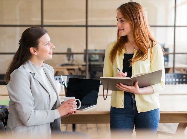 Glückliche attraktive frau zwei, die am arbeitsplatz zusammenarbeitet