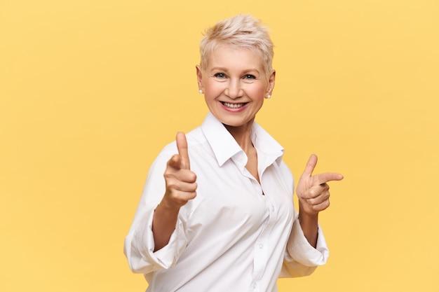 Glückliche attraktive fünfzigjährige frau, die stilvolles weißes hemd trägt, das vorderfinger zeigt und lächelt, sie wählt, mit ihr zu tanzen, mit breitem strahlendem lächeln schauend. körpersprache