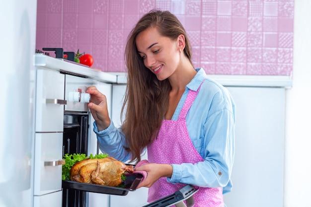 Glückliche attraktive hausfrau in der schürze, die ganzes huhn im ofen backt. ente zum abendessen kochen