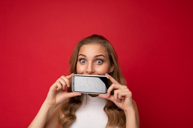 Glückliche attraktive junge blonde weibliche person mit weißem t-shirt isoliert auf rotem hintergrund mit kopienraum mit smartphone, das telefon in der hand mit leerem bildschirm für ausschnitt mit blick auf die kamera zeigt.
