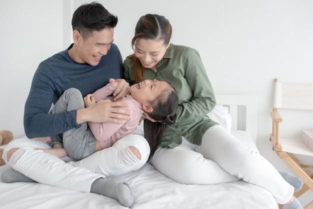 Glückliche attraktive junge familie, welche die tablette aufpasst