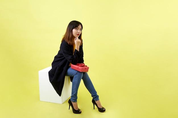 Glückliche attraktive junge frau, die auf leere leere box sitzt, die rote geschenkbox auf gelbem raum hält