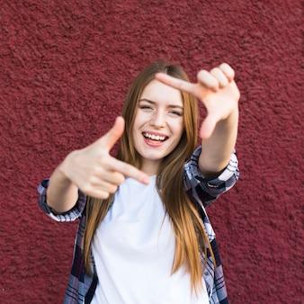 Glückliche attraktive junge frau, die handrahmen gegen rote wand macht