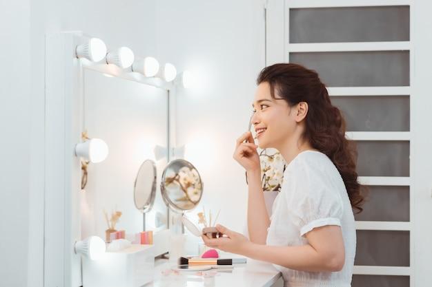 Glückliche attraktive junge frau, die kosmetik auf gesicht nahe kosmetischem tisch am morgen anwendet