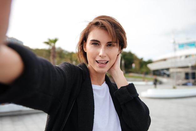 Glückliche attraktive junge frau, die selfie im freien nimmt