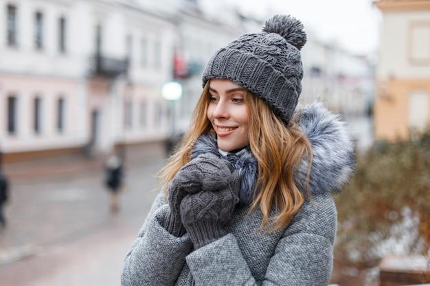 Glückliche attraktive junge frau in einer winterstrickmütze in einem trendigen grauen mantel mit fell in gestrickten warmen handschuhen mit einem schönen lächeln geht an einem wintertag durch die stadt. fröhliches mädchen genießen einen spaziergang.