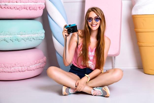Glückliche attraktive junge frau mit lustigen herzen sonnenbrille, lächelnd und foto vor der kamera. atemberaubende junge blonde fotografin mädchen posiert in der nähe von gefälschten makronen und eis. auf dem boden sitzen.