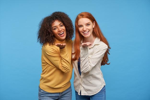 Glückliche attraktive junge freundinnen, die sich umarmen und breit lächeln, während sie fröhlich schauen, ihre handflächen erhoben halten, während sie über der blauen wand posieren