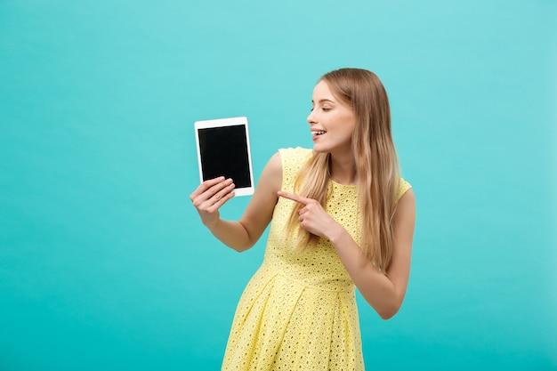 Glückliche attraktive kaukasische frau, die mit dem finger auf dem tablet auf den kopierraum zeigt, der auf blauem hintergrund isoliert ist?