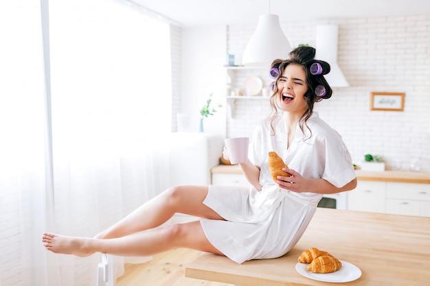 Glückliche attraktive nette junge haushälterin sitzen auf tisch in der küche. laut lachen. weiße tasse in händen halten. vor der kamera posieren. sorglose frau auf dem bild.