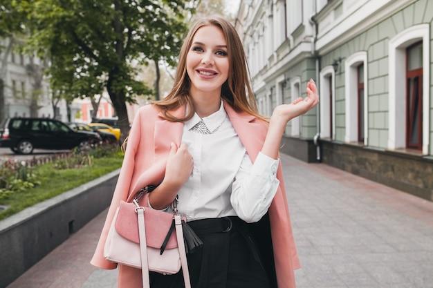 Glückliche attraktive stilvolle lächelnde frau, die stadtstraße im rosa mantel geht