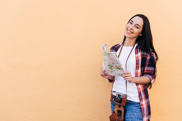 Glückliche attraktive tragende kamera der jungen frau und halten der karte, die nahe pfirsichwand steht