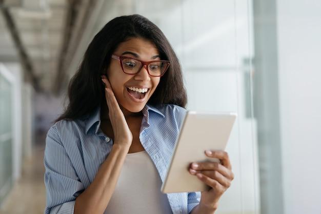 Glückliche aufgeregte afroamerikanerfrau, die digitales tablett verwendet, das gute nachrichten liest, videos ansieht
