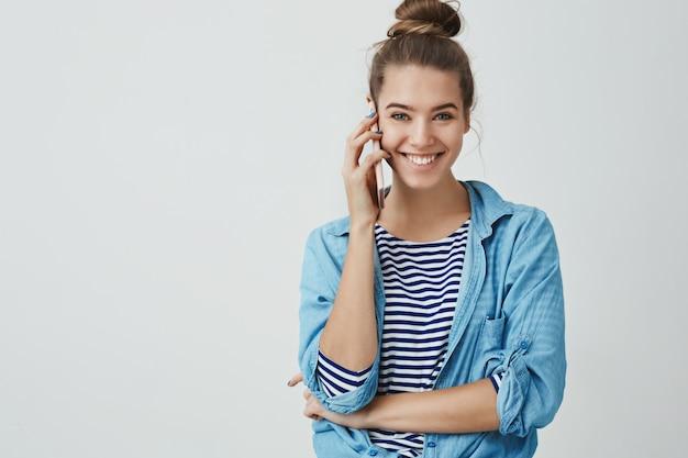 Glückliche aufgeregte attraktive junge frau, die per telefon spricht