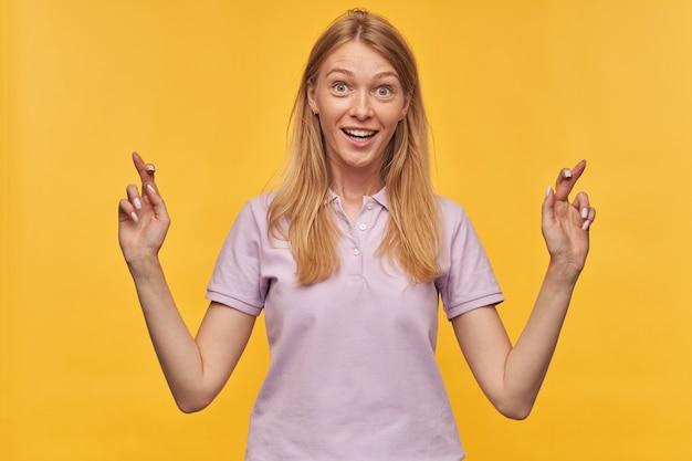 Glückliche aufgeregte blonde junge frau mit sommersprossen in lavendel-t-shirt drückt die daumen und wünscht sich über die gelbe wand blick in die kamera