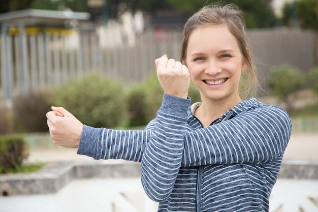 Glückliche aufgeregte eignungsfrau, die draußen trainiert