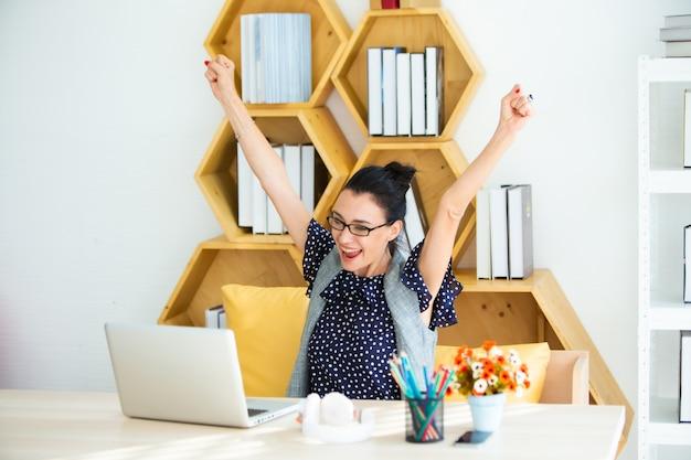 Glückliche aufgeregte erfolgreiche schöne geschäftsfrau, die im modernen büro mit laptop, glückliche haltung des erfolgs triumphiert