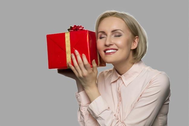 Glückliche aufgeregte frau erhielt geburtstagsgeschenk. freudige dame, die geschenkbox auf grauem hintergrund hält. geschenke vom geliebten mann.