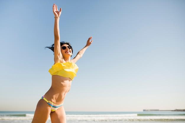 Glückliche aufgeregte frau im gelben bikini, der ihre hände am strand gegen blauen klaren himmel anhebt