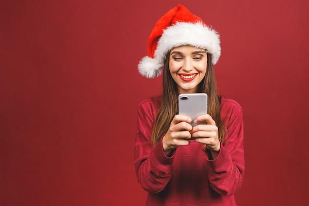 Glückliche aufgeregte frau im roten weihnachtsmannhut mit handy