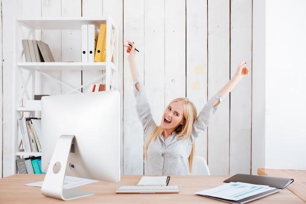 Glückliche aufgeregte geschäftsfrau, die erfolg feiert, während sie mit erhobenen händen an ihrem arbeitsplatz sitzt