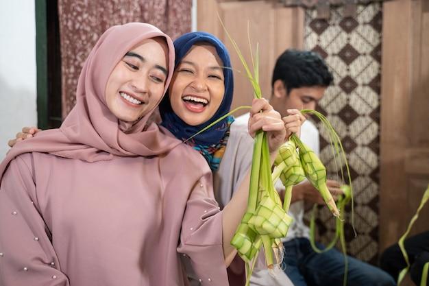 Glückliche aufgeregte gruppe von freunden und familie, die zusammen ketupat für eid fitr mubarak oder idul fitri lebaran tradition machen