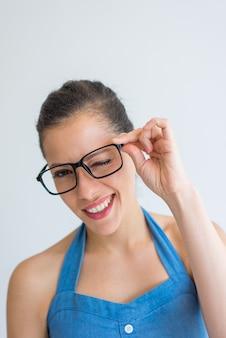 Glückliche aufgeregte junge frau, die brillen justiert und an der kamera blinzelt.
