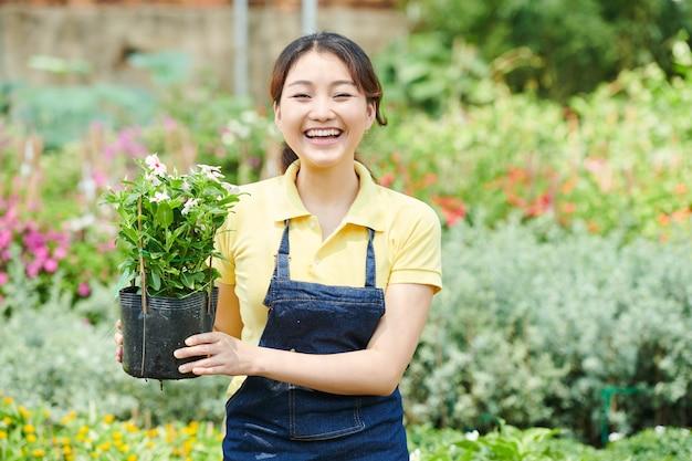 Glückliche aufgeregte junge frau, die topf mit blühender pflanze hält, wenn sie im gartencenter steht