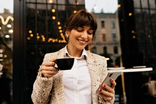 Glückliche aufgeregte junge frau gekleidete weiße jacke verwendet smartphone und kopfhörer, während kaffee auf stadtlichthintergrund hochqualitatives foto trinkt