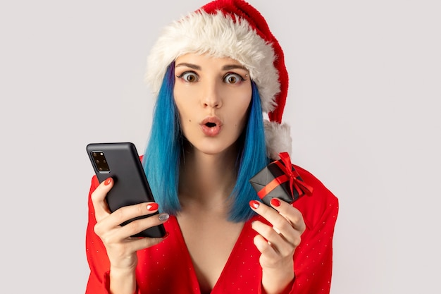 Glückliche aufgeregte junge frau im weihnachtsmannhut mit geschenkbox und smartphone über grauem hintergrund. weihnachts-online-shopping-verkaufskonzept