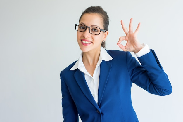 Glückliche aufgeregte junge geschäftsfrau in den brillen, die okayzeichen zeigen.