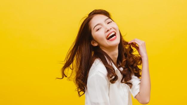 Glückliche aufgeregte junge lustige asiatische dame, die musik hört und in der freizeitkleidung über gelber wand tanzt. menschliche gefühle, gesichtsausdruck, studioporträt, lebensstilkonzept.