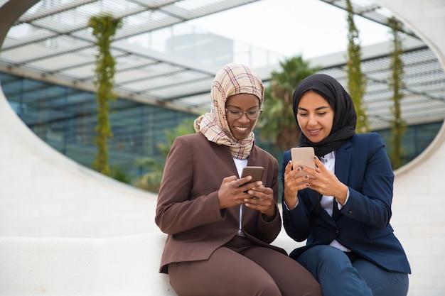 Glückliche aufgeregte kollegen, die auf smartphones plaudern