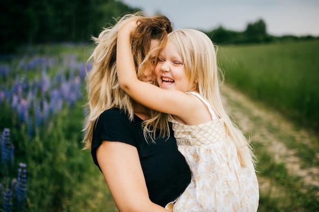 Glückliche aufgeregte mutter, die ihre schöne lächelnde kleine blonde tochter auf dem sommergebiet umarmt.