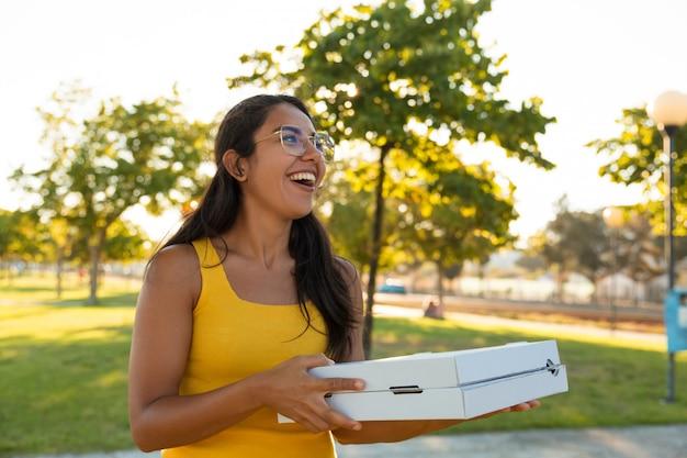 Glückliche aufgeregte tragende pizza der jungen frau für party im freien