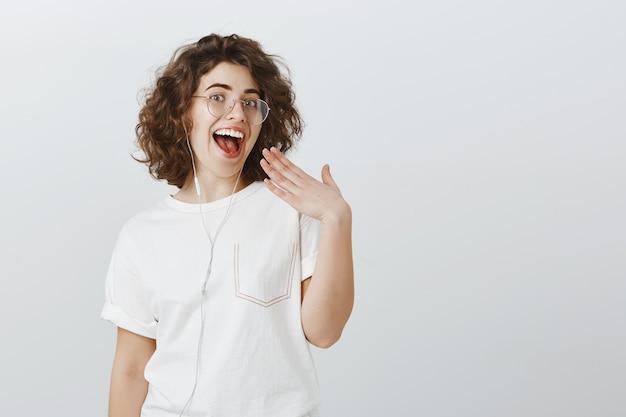 Glückliche ausgehende junge frau, die weiße zähne lacht und lächelt, musik in kopfhörern hört, kopfhörer trägt, um zu kommunizieren