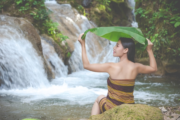 Glückliche badende frauen am natürlichen wasserfall