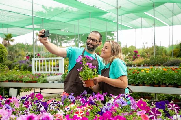 Glückliche bauern, die selfie mit blühender petunienpflanze nehmen